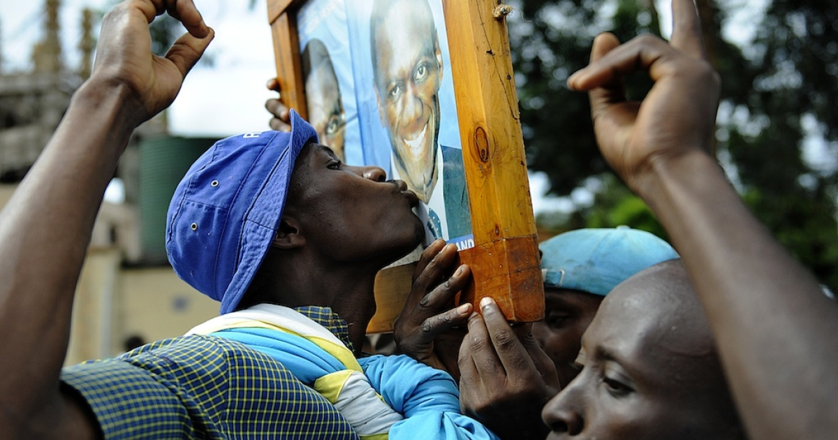 A supporter kisses a portrait of Ugandan opposition leader Kizza Besigye, who was arrested Monday during a