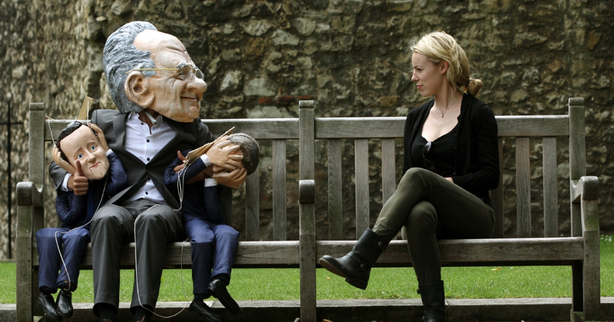 A demonstrator (L) dressed in a Rupert Murdoch mask while holding puppets of British Prime Minister David Cameron and British Minister for Culture, Media and Sport Jeremy Hunt, is pictured during a protest against Murdoch's proposed takeover of BSkyB, in London on July 8, 2011.</p>