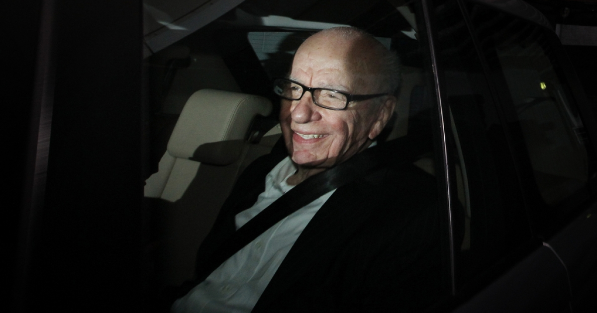 Rupert Murdoch, Chief Executive Officer of News Corp., smiles at photographers as he is driven from News International's headquarters on July 13, 2011 in London, England.</p>