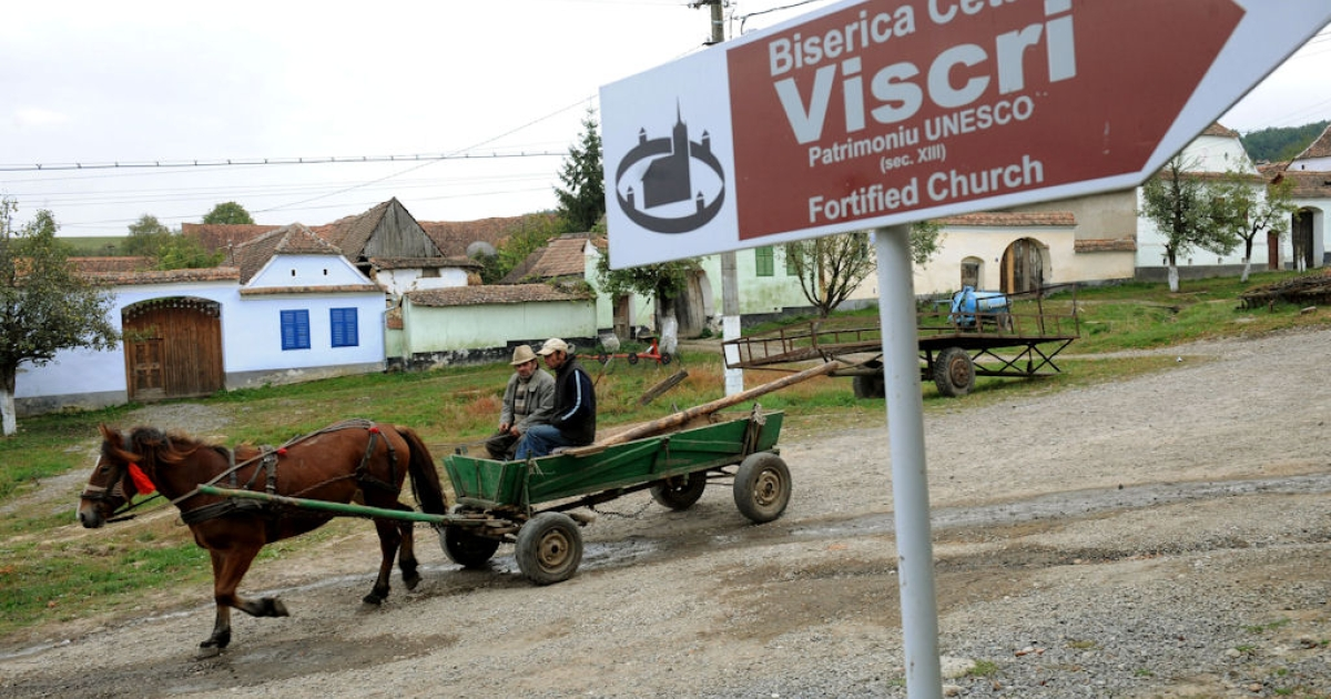 Men ride a carriage in Viscri, Romania, on Oct. 8, 2010. More than 11,000 tourists from around the world came in 2009 to see Viscri's pastel-coloured houses and its UNESCO World Heritage fortified church.</p>