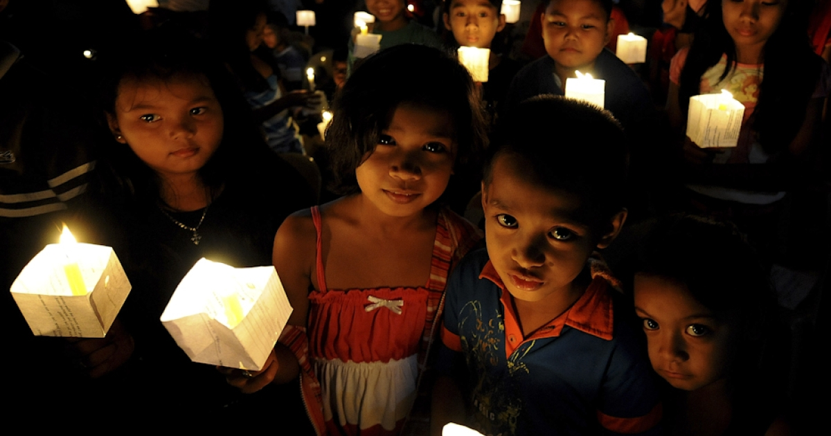 Children hold lighted candles during a prayer for Justice and Protection against Sex Trafficking of Children and Young People in Quezon City suburban Manila on December 12, 2010, as part of the annual observance of International Day against Human Trafficking. Cybersex dens are a growing problem in the impoverished Southeast Asian nation that has long struggled to curb child prostitution, according to law enforcers and social workers.</p>