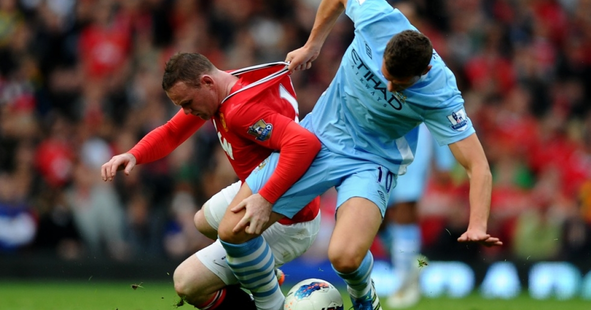 Edin Dzeko of Manchester City tangles with Wayne Rooney of Manchester United during the Barclays Premier League match at Old Trafford on October 23, 2011 in Manchester, England. Did a billionaire's cash lead to the 6 to 1 trouncing?</p>