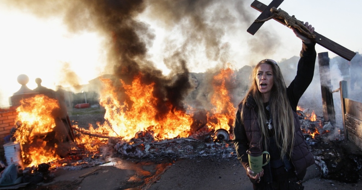 A resident protests during the eviction of the Dale Farm traveler site in Essex, south-east England.</p>