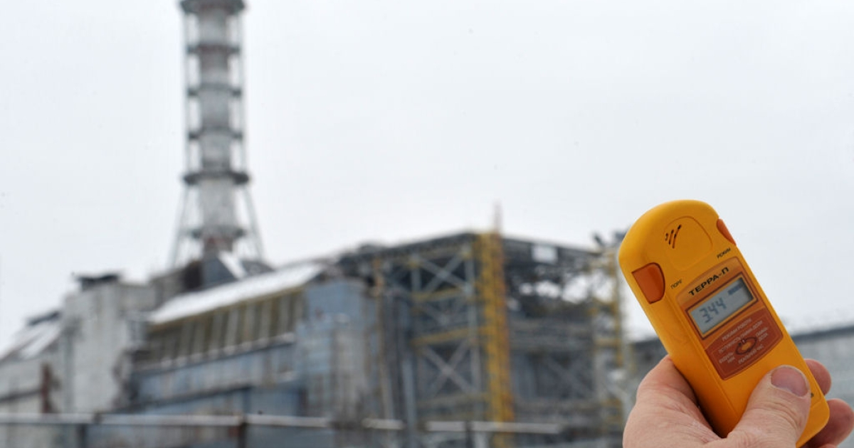 A man holds a geiger counter in front of the sarcophagus covering the destroyed fourth block of the Chernobyl nuclear power plant on Feb. 24, 2011 ahead of the 25th anniversary of the meltdown of reactor number four due to be marked on April 26, 2011.</p>