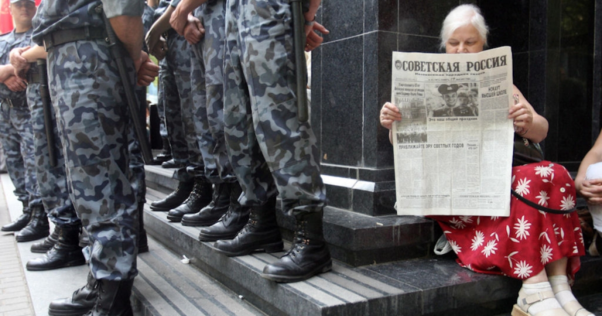 A woman reads a newspaper as she sits near the entrance of the General Prosecutor's office guarded by special police during a rally in Kiev, Ukraine on May 25, 2007.</p>