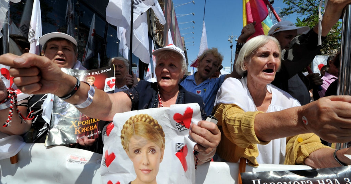 Supporters of Yulia Tymoshenko raise their fists during a rally in front of the court where she is currently being tried, in Kiev, on July 22, 2011.</p>