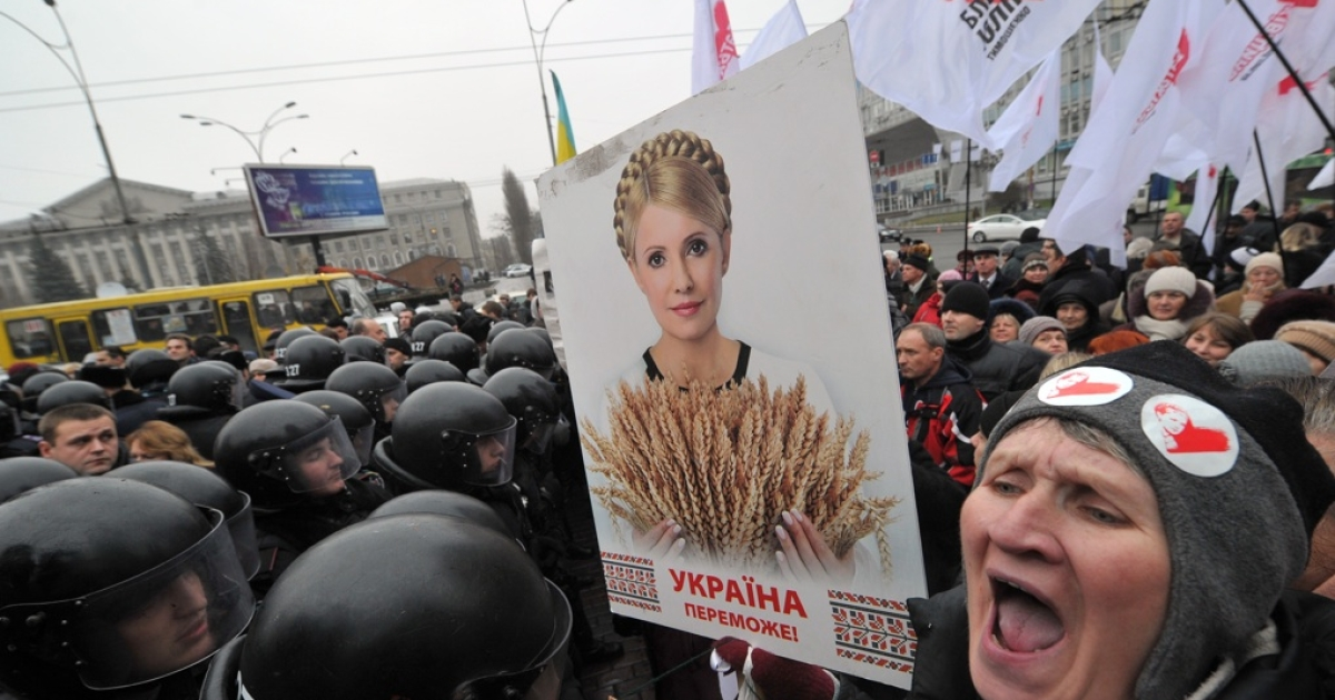 A supporter of Ukraine's former Prime Minister Yulia Tymoshenko shouts as she holds a picture of the opposition leader during a rally in front of a court in Kiev on Dec. 14, 2011.</p>