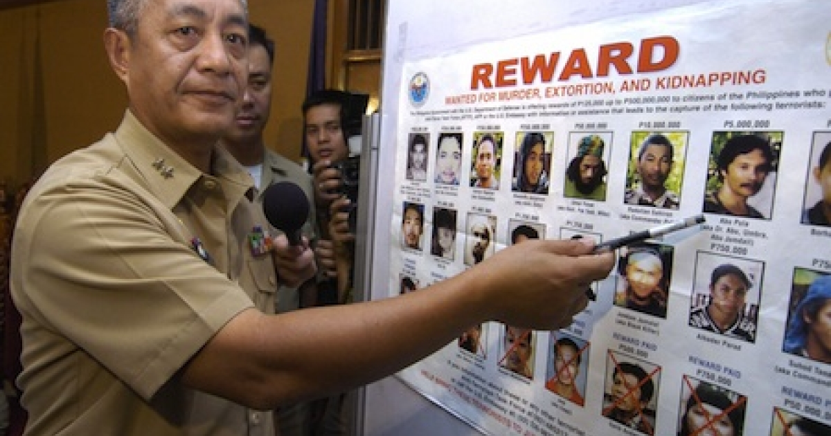 A Philippine Marine Corps commandant points to photos of Abu Sayyaf Muslim extremists, who were believed to be sheltering Umar Patek, allgedly involved in the 2002 Bali bombings that killed over 200 people.</p>