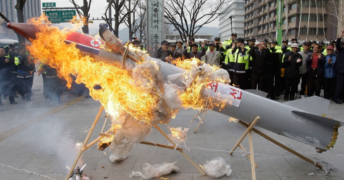 South Korean conservative protesters burn a mockup of a North Korean missile during an anti-North Korea rally protesting against North Korea launching the long-range missile on April 13, 2012 in Seoul, South Korea.</p>