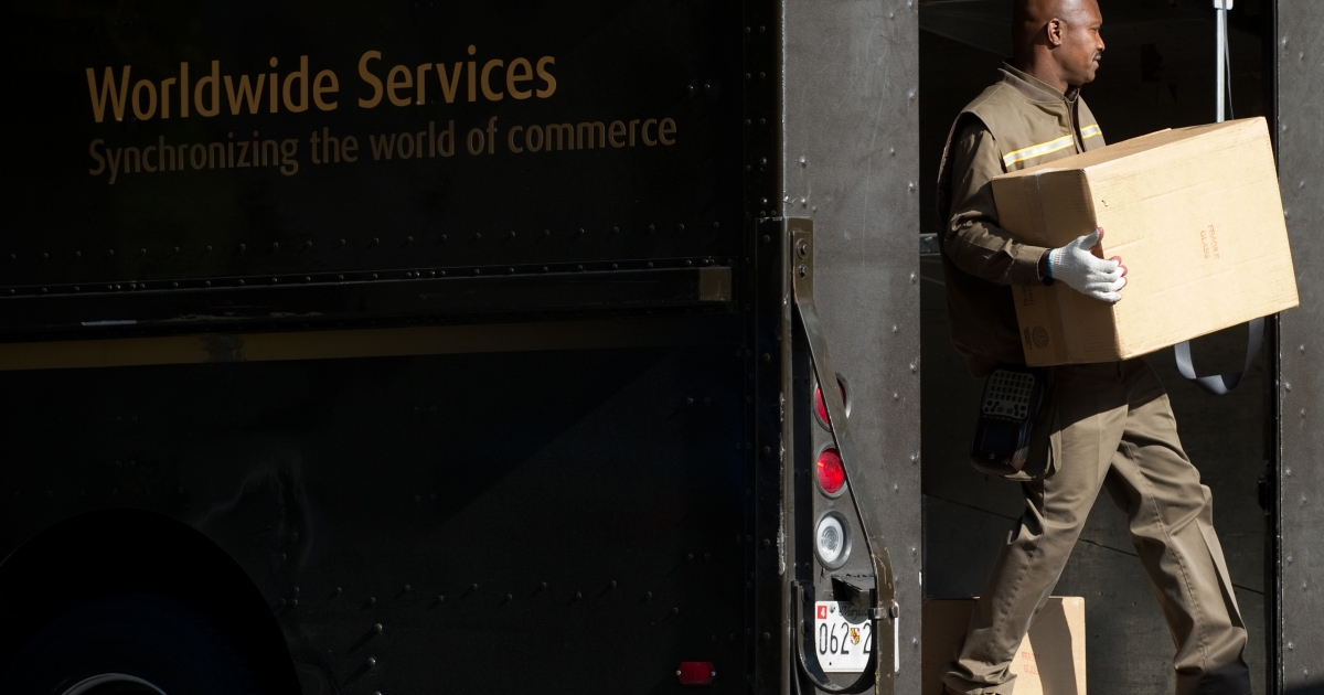 A United Parcel Service delivery man unloads boxes from his truck outside a business in Washington, DC, on Nov. 5, 2010.</p>