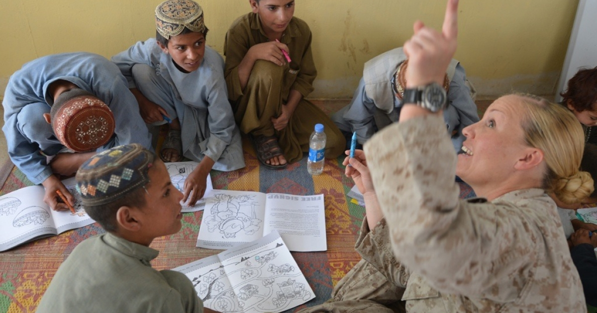 USN Hospital Corspman Amy Housley, right, gestures during a class for Afghan children given by the US Marines Female Engagement Team (FET) from the 1st battalion 7th Marines Regiment on June 7, 2012. The US-led war in Afghanistan has cost the lives of around 3,000 US and allied troops, seen thousands of Afghans killed and cost hundreds of billions of dollars.</p>