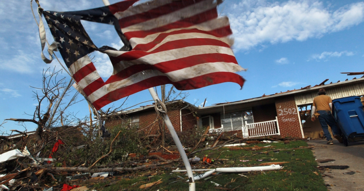 A torn American flag hangs on a pole outside of a house that was damaged during a massive tornado on May 27, 2011 in Joplin, Missouri.</p>