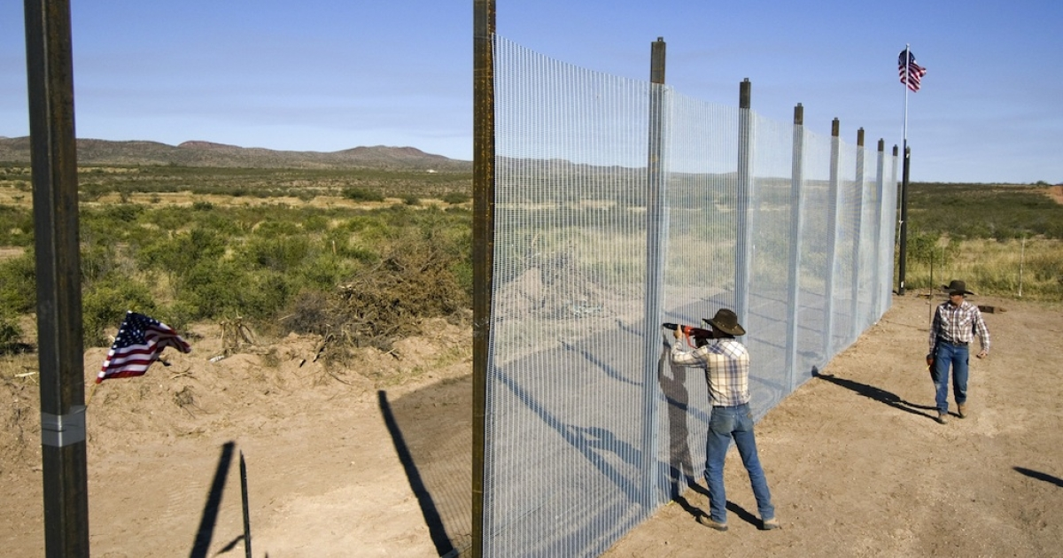 This picture taken on October 20, 2006, shows workers building a 14-foot high mesh fence along the US-Mexican border near Naco, Arizona.</p>