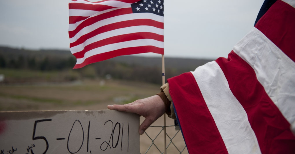 Jeff Ray, of Shanksville, Pa., holds a homemade sign and looks over the crash site of Flight 93 following the announcement that Osama Bin Laden had been killed. Nearly 10 years after September 11, 2001, construction is underway to erect a formal memorial at the crash site.</p>