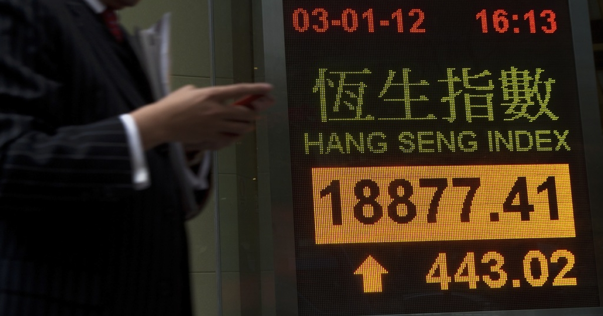 A man looks at his phone as he walks by an electronic display showing the Hang Seng Index closing figures in Hong Kong on January 3, 2012.</p>