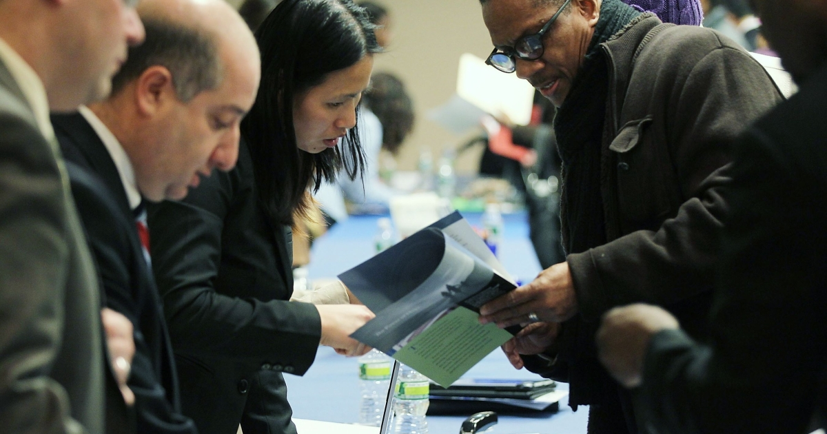 Job seekers speak with prospective employers at a December 2011 career fair in New York City.</p>