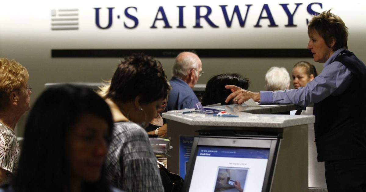 Travelers check-in at the US Airways ticket counter on April 19, 2012.</p>