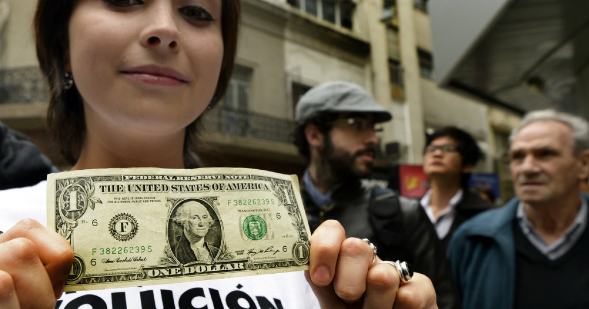 A demonstrator, member of the fictitius Liberal Libertarian Party, offers one dollar bills for a better rate than the official as a protest against the government, in downtown Buenos Aires.  The US dollar is now on the rise, and might offer a better rate for everyone.</p>