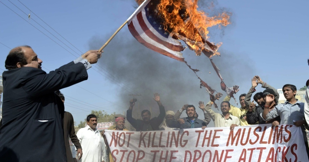 A Pakistani protester holds a burning US flag at a protest against US drone attacks in Multan on February 9, 2012.</p>