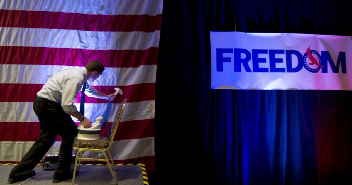 A campaign worker of Republican presidential candidate, former Pennsylvania Sen. Rick Santorum works irons the flag before a rally in Mars, Pennsylvania on April 3, 2012.</p>