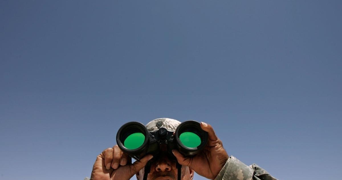 A National Guard specialist spots three men near the U.S.-Mexico border near Sunland Park, New Mexico, on June 26, 2007.</p>