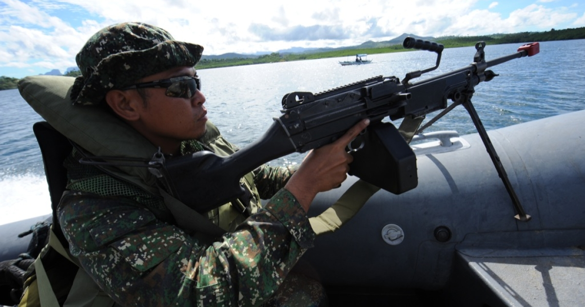 A Philippine marine aboard their boat, conduct security patrol along Ulugan Bay, facing South China Sea in Puerto Princesa, Palawan island, south of Manila on April 25, 2012.</p>