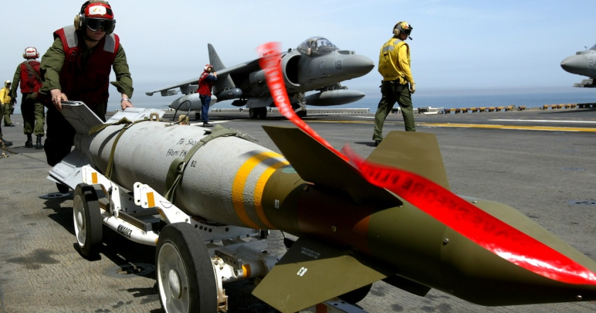 An ordnance hadler moves a 500 pound GBU-12 precision guided bomb as a U.S. Marines AV-8B Harrier jet taxis on the flight deck of the U.S.S. Bon Homme Richard  in the Persian Gulf in 2003.</p>