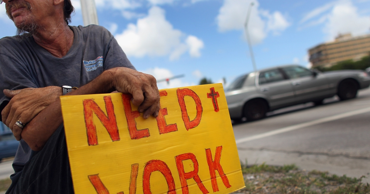 Stephen Greene works a street corner hoping to land a job as a laborer or carpenter on June 3, 2011 in Pompano Beach, Florida.</p>
