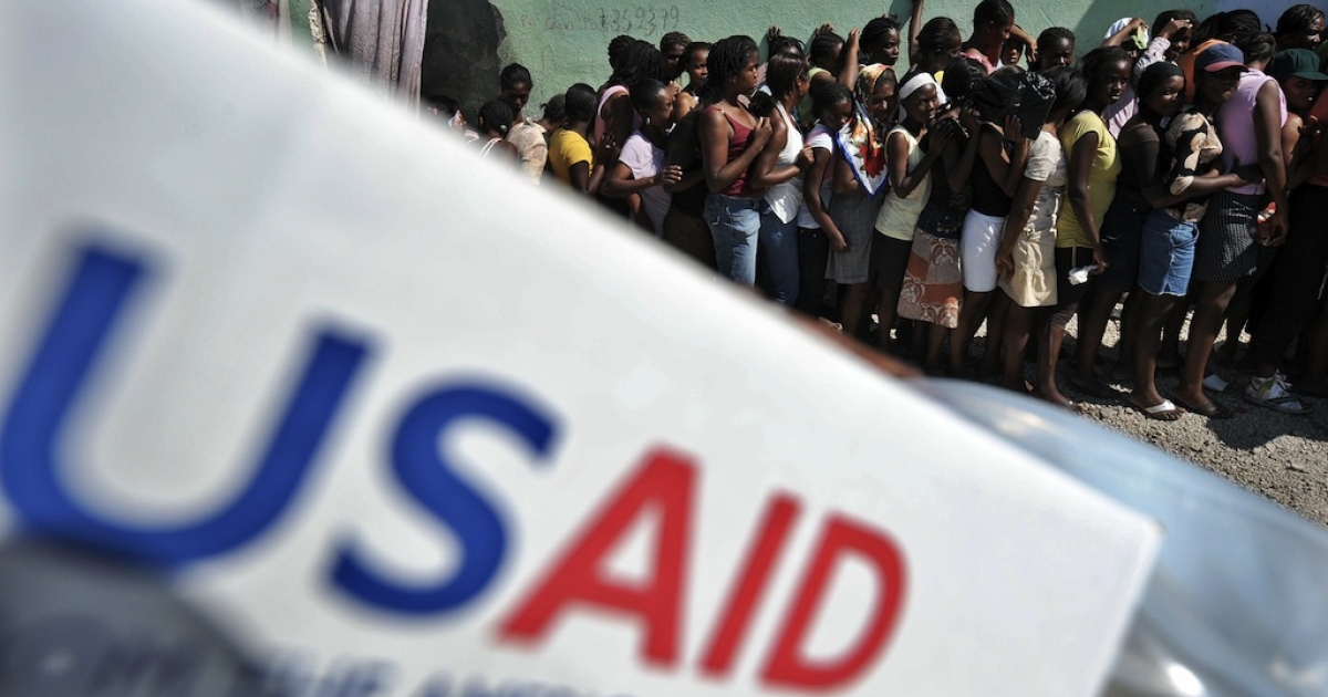 People line up to receive items at a USAID distribution point in Port-au-Prince following the massive 7.0-magnitude quake that shattered Haiti. However, many believe the West's pattern of unfettered aid is actually contributing to the problem of dependence and making development impossible.</p>