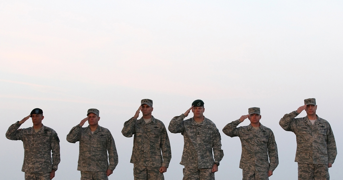 US military oficers salute during a dignified transfer fat Dover Air Force Base.</p>
