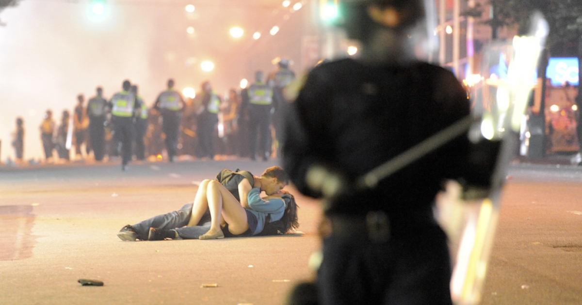 Riot police walk in the street as a couple kiss on June 15, 2011 in Vancouver, Canada. Vancouver broke out in riots after their hockey team the Vancouver Canucks lost in Game Seven of the Stanley Cup Finals. This