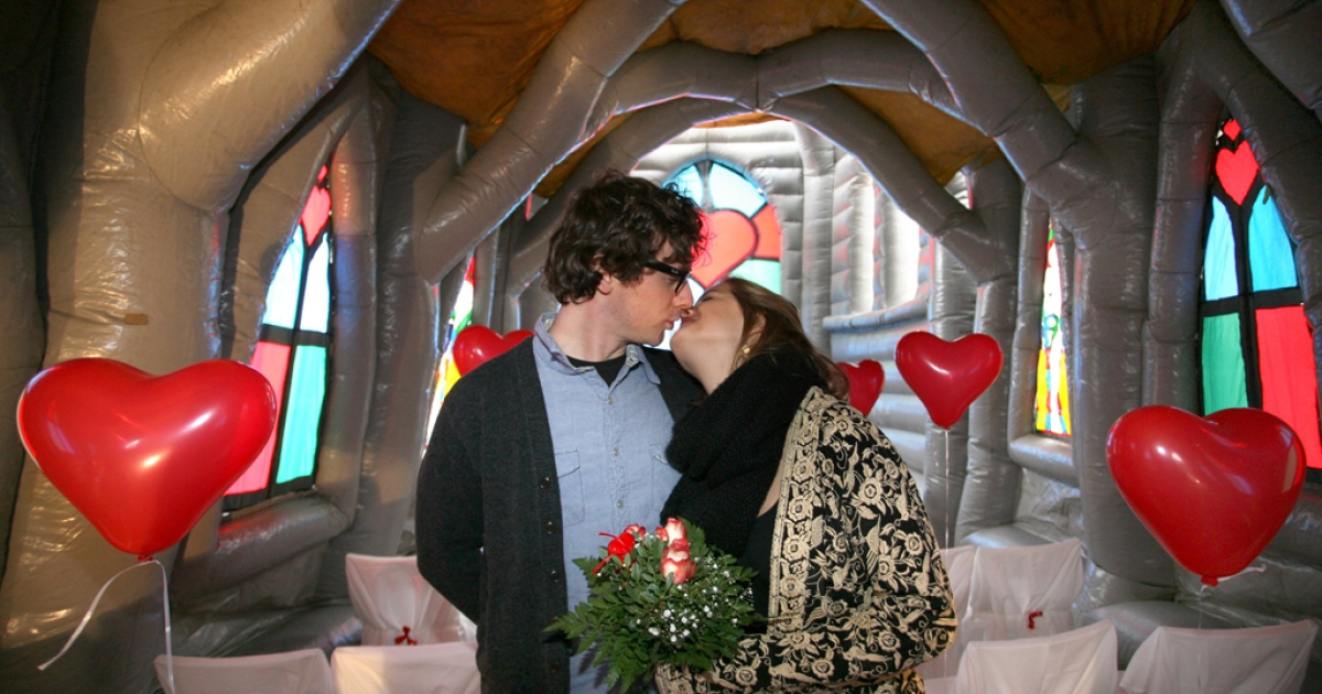 Pia Walter and Maxence Lepesant kiss in an inflatable church during their wedding rehearsal on Februray 14, 2012. Los Angeles County's registrar has sped up the marriage process on Valentine's Day, their busiest day of the year.</p>