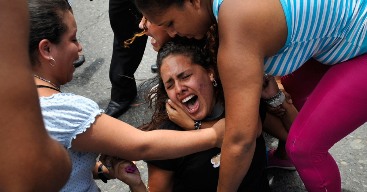 Relatives of inmates of El Rodeo I and II penitentiaries cry outside the prisons compounds in Guatire, outskirts of Caracas.</p>