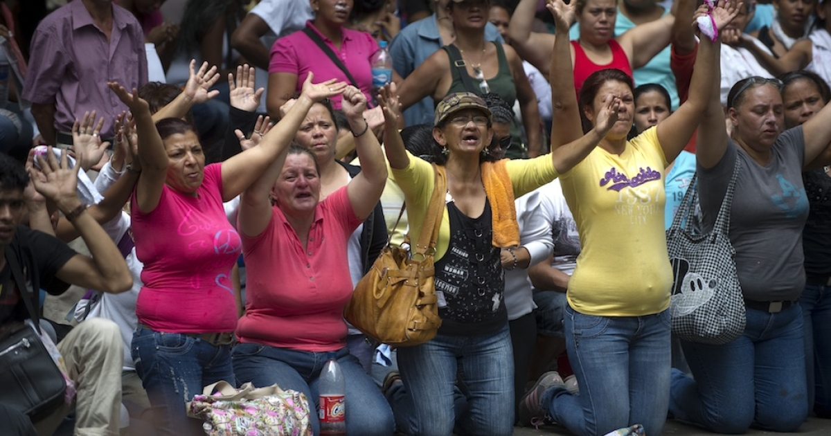 Relatives of inmates kneel during a demonstration after a riot in front of La Planta prison in Caracas on April 30, 2012. The authorities of the Ministry of Correctional Services are trying to negotiate voluntary transfers to other prisons.</p>