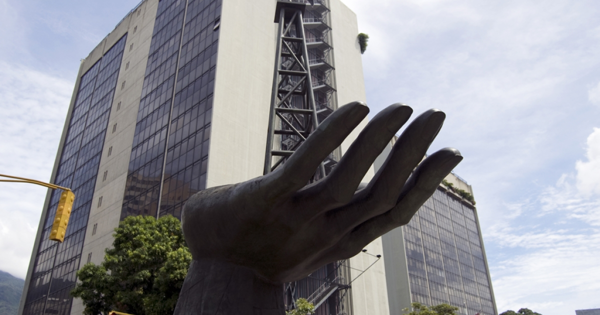 A statue of a hand with an oil drilling rig out front of Venezuela's state oil company PDVSA.</p>