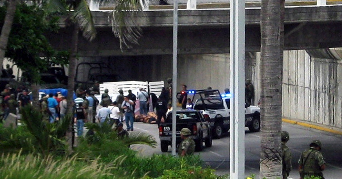 Officials swarm the scene in Veracruz, where 35 bodies were dumped in the street.</p>
