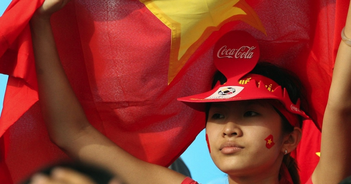 A young Vietnamese girl shields herself with a national flag at a Hanoi stadium.</p>