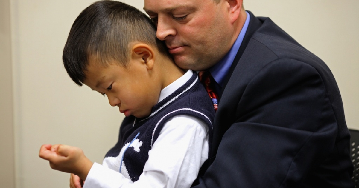 Noah Avery, 4, is held by his adopted father Alex Avery of Stanton, Virginia, during the children's citizenship ceremony at the U.S. Citizenship and Immigration Services office November 14, 2011 in Fairfax, Virginia. Twenty-five children from nine countries, including Bulgaria, China, Ethiopia, Guatemala, Korea, Liberia, Russia, Taiwan and Vietnam, celebrated their U.S. citizenship during the ceremony.</p>
