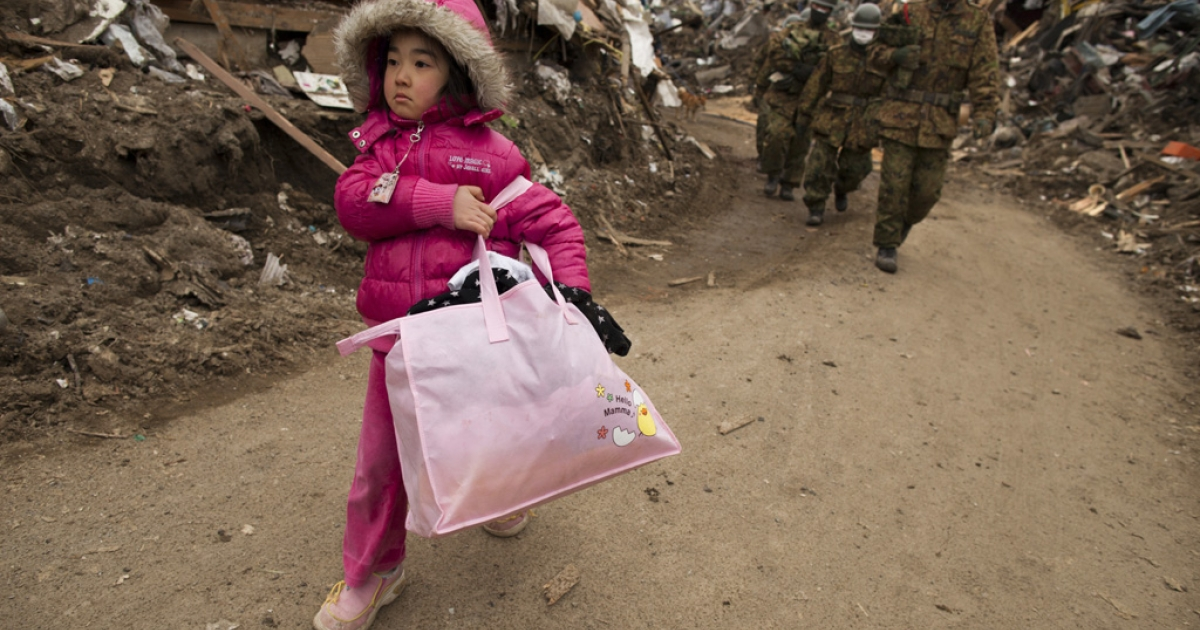 Neena Sasaki, 5, carries some of the family belongings from her home that was destroyed after the devastating earthquake and tsunami on March 15, 2011 in Rikuzentakata, Miyagi province, Japan.</p>