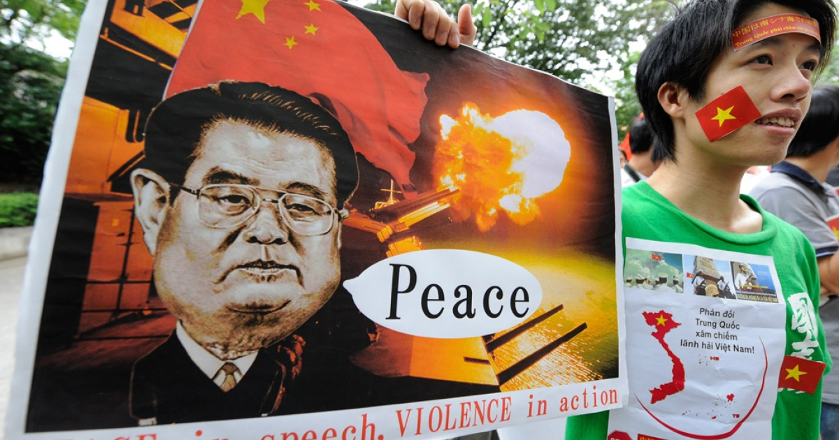 A Vietnamese youth holds up a placard during a rally denouncing China over the recent rise in tensions over territorial claims in the South China Sea on June 25, 2011.</p>