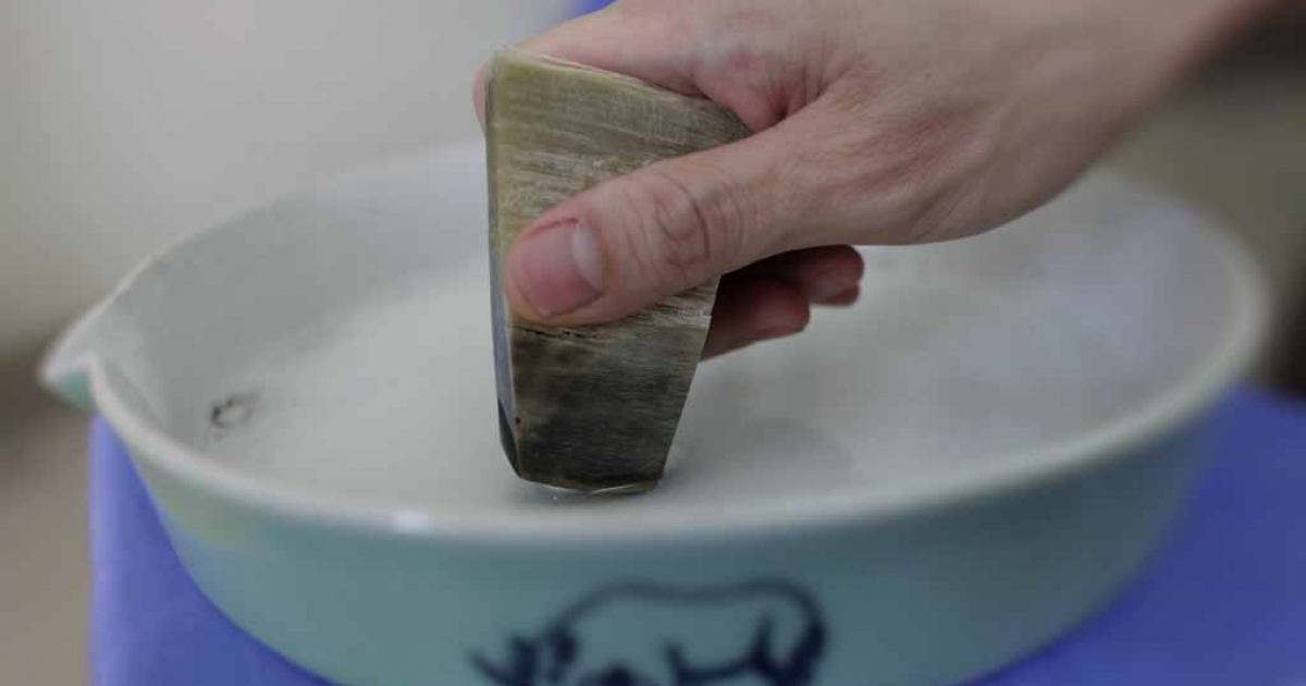A man shows how to use the ceramic grinding plate with a piece of rhino horn in Hanoi on April 24, 2012 .</p>