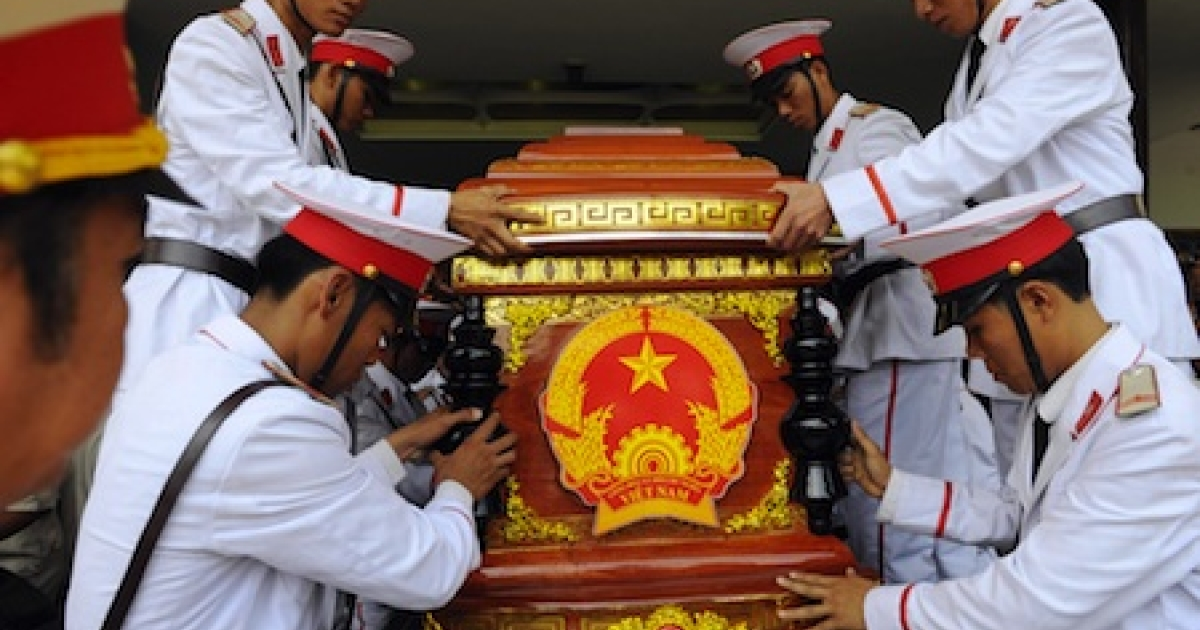 Guards lower a coffin during a burial service in Ho Chi Minh City in 2005.</p>
