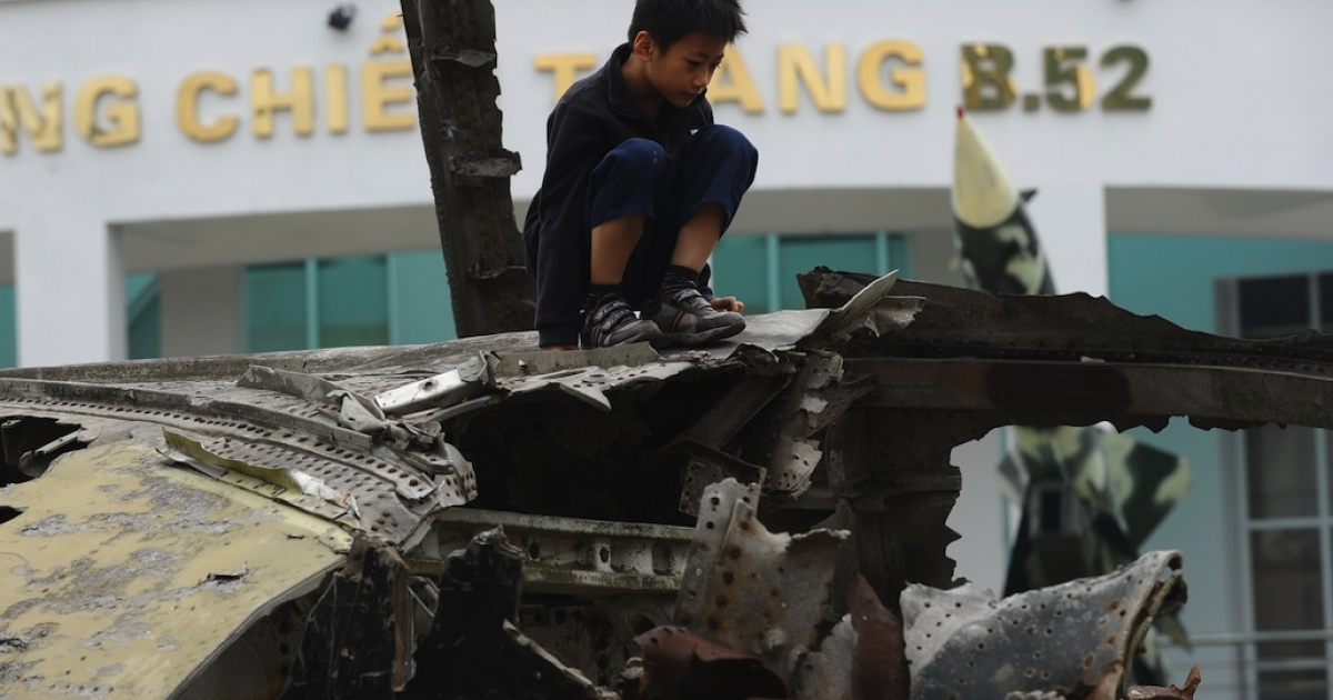 A boy sits on top of wreckage of a downed US Air Force B-52 aircraft on display in Hanoi, Vietnam, on December 19, 2012.</p>