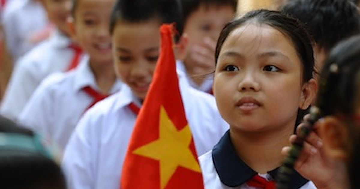 A student holds a flag during a ceremony marking the new school year at a local elementary school in downtown Hanoi on September 5, 2012.</p>
