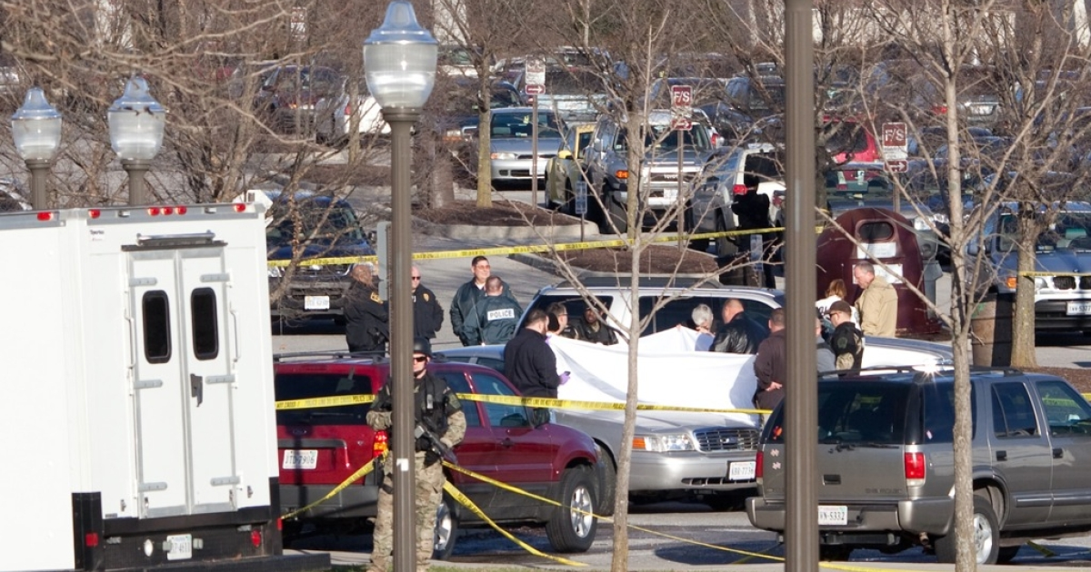 Police officers gather around the scene of a shooting in front of Cassell Coliseum on the Virginia Tech campus December 8, 2011 in Blacksburg, Virginia.</p>