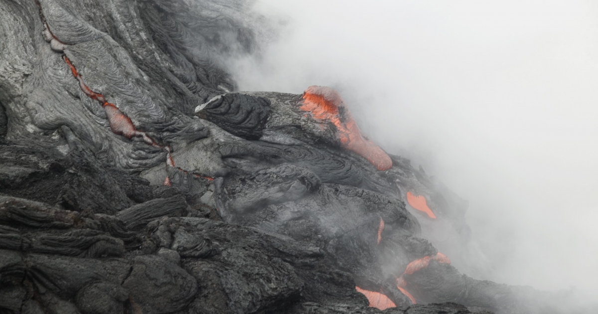 Lava flows into the ocean from Kilauea Volcano at Volcanoes National Park in Hawaii on June 6, 2004.</p>