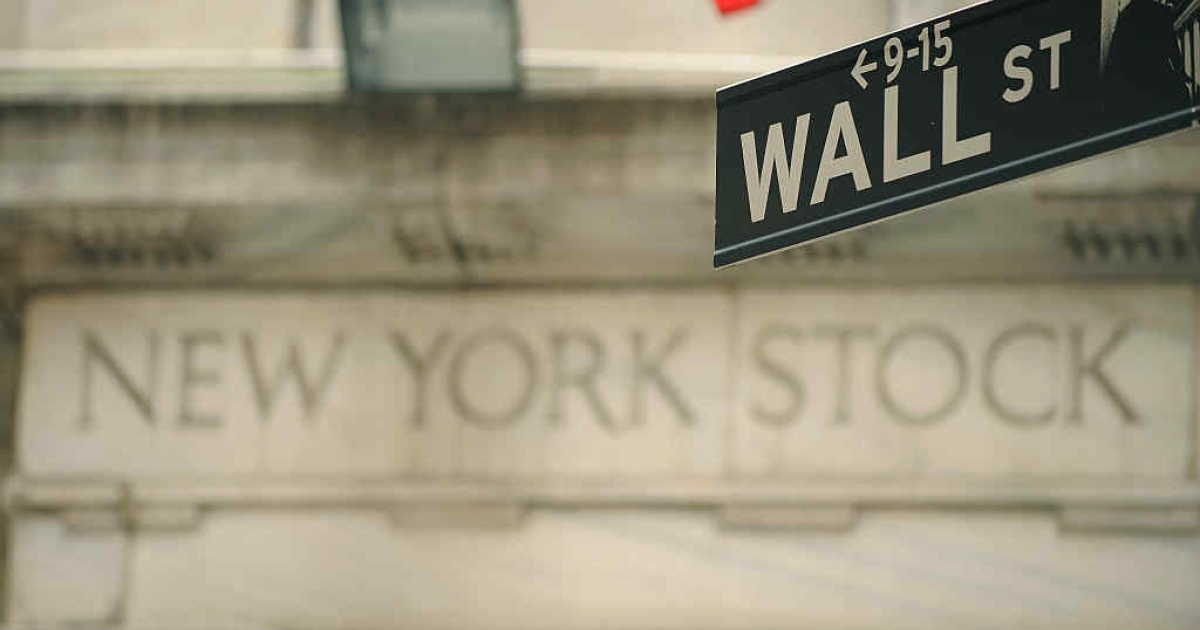 Wall Street sign outside an entrance of the New York Stock Exchange.</p>