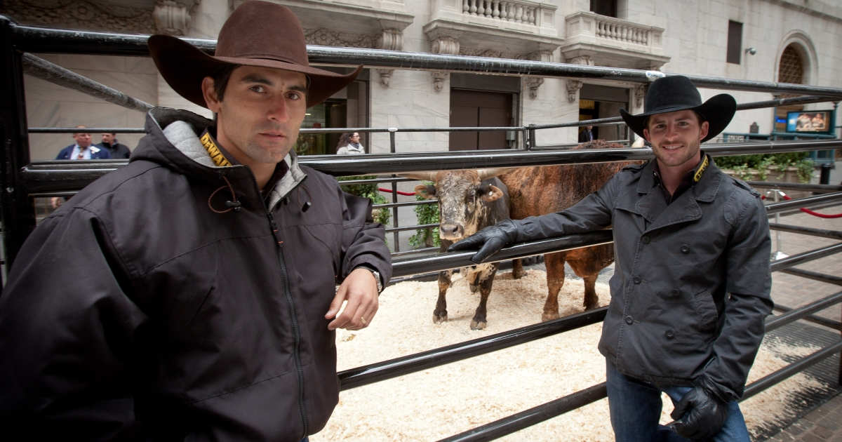 In this handout photo provided by NYSE Euronext, Silvano Alves (L), 2011 the PBR World Champion, bull rider, and Douglas Duncan, a bull rider with professional Bull Riders Inc., visit the NYSE. They helped ring the closing bell on Jan 5, 2012 in New York City.</p>