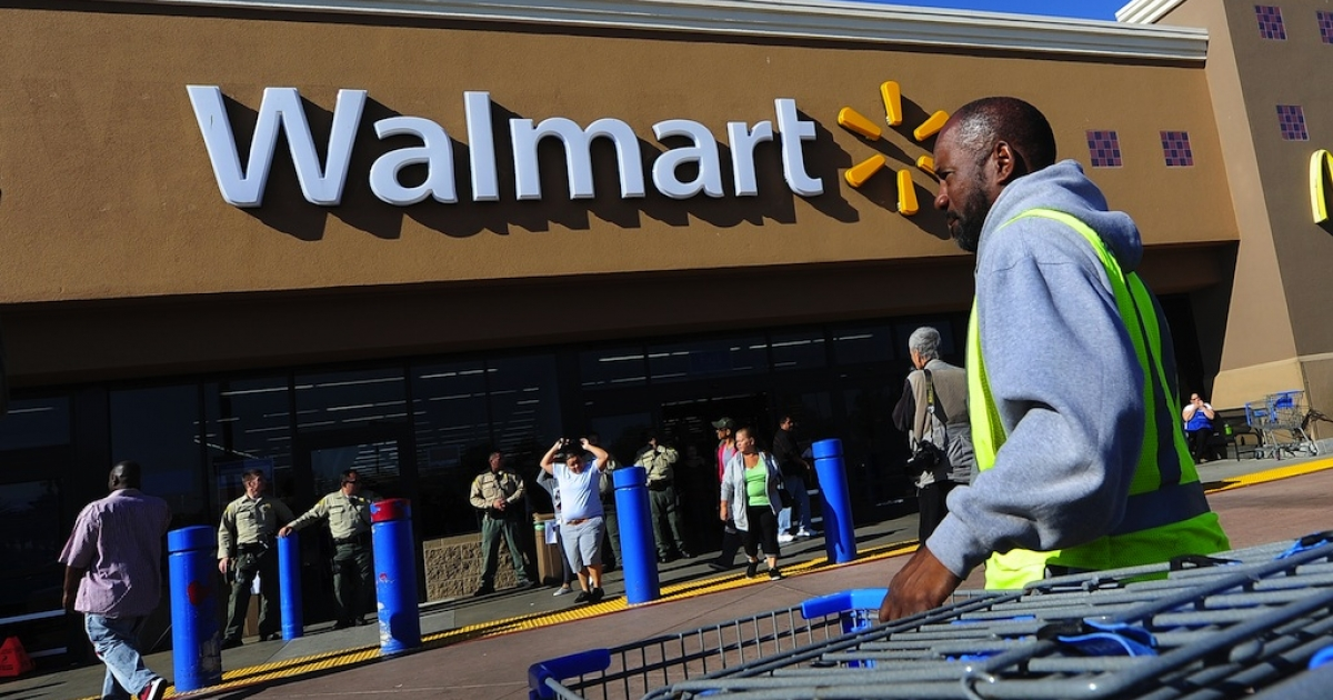 A Walmart employee gathers trolleys in Paramount, California, on Black Friday.</p>