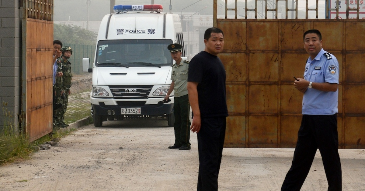 Chinese police wait outside the Beijing No. 2 prison after the release of dissident Wang Xiaoning on August 31, 2012.</p>